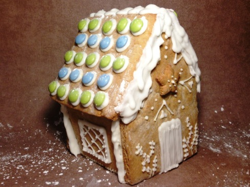 christmas gingerbread house with smarties roof and white royal icing piping