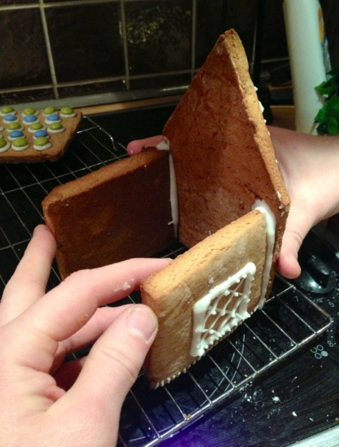 gingerbread house assembly with white royal icing holding up with hands