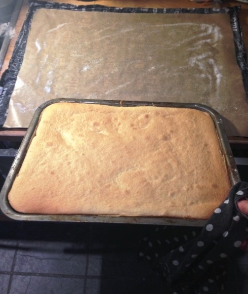 baked swiss roll cake turning out onto sugared baking sheet