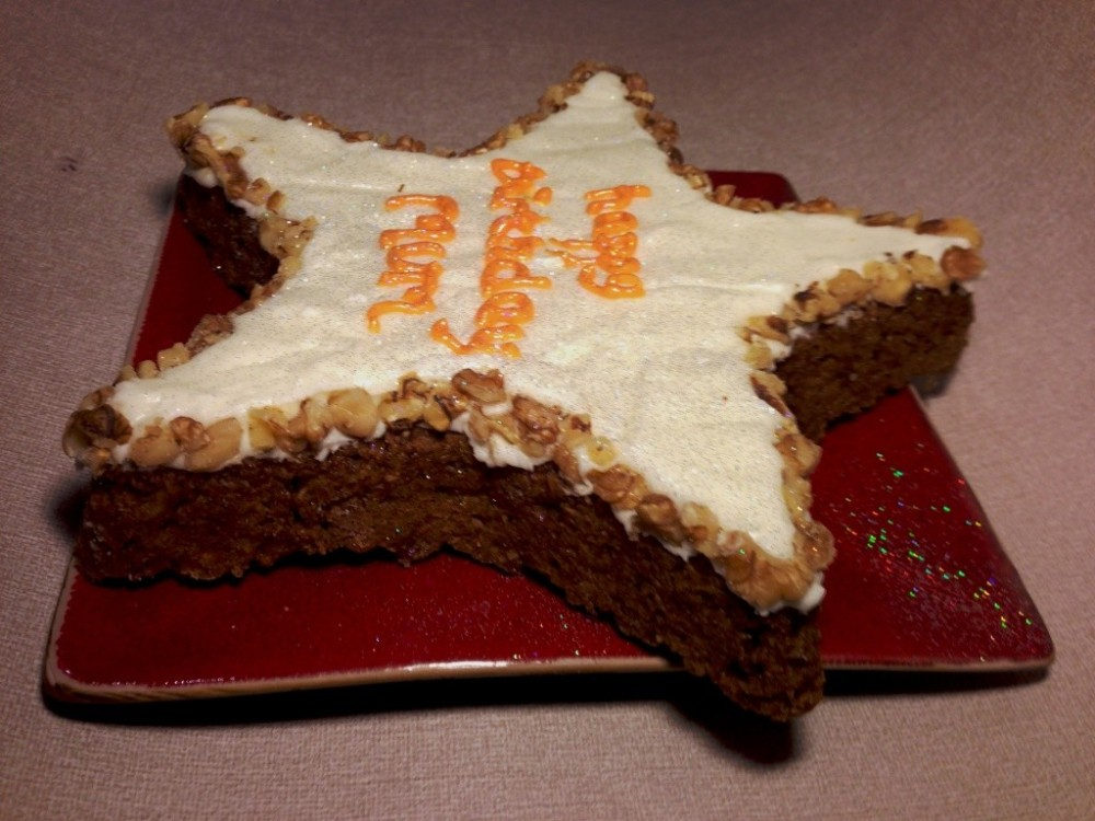 carrot cake star shaped with cream cheese icing and walnut pieces edging happy birthday