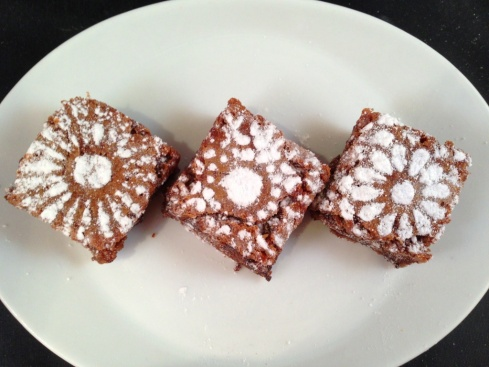 belgian chocolate brownie squares with icing sugar flower patterns stenciled