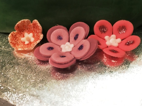 fondant icing edible flowers with glitter edging pink orange purple