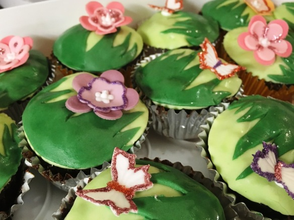garden themed cupcakes flowers and butterflies on green grass fondant topping